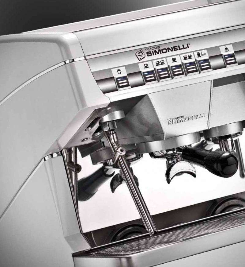 Image is a closeup view of the Nuova Simonelli Appia II Compact 2 group espresso machine in Whie, with traditional brew group height and volumetric dosing controls.