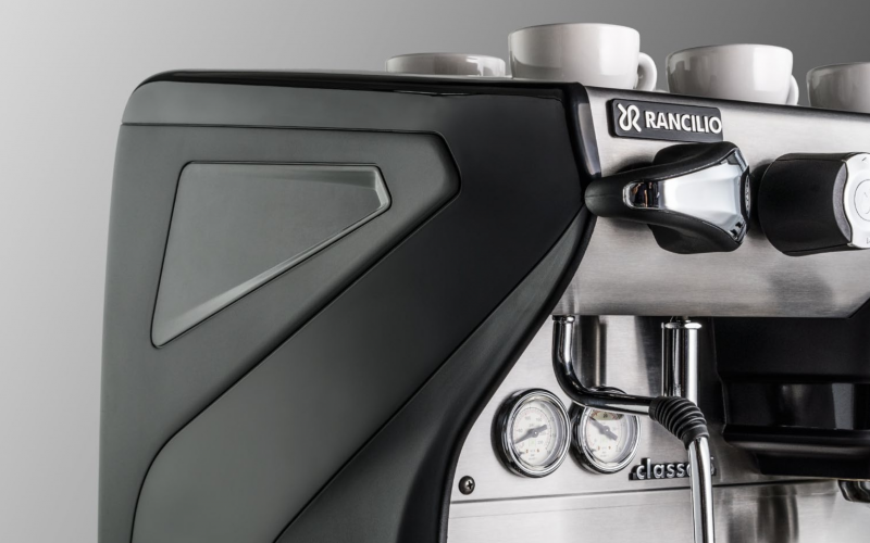 This image is a closeup front-side view of the Rancilio Classe 5 espresso machine steam wand, steam c-lever, gauges and side panels.