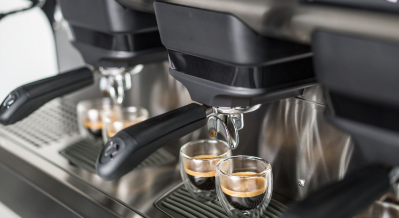 This image is a closeup front view of the Rancilio Classe 5 espresso machine brew groups, with traditional brew group.