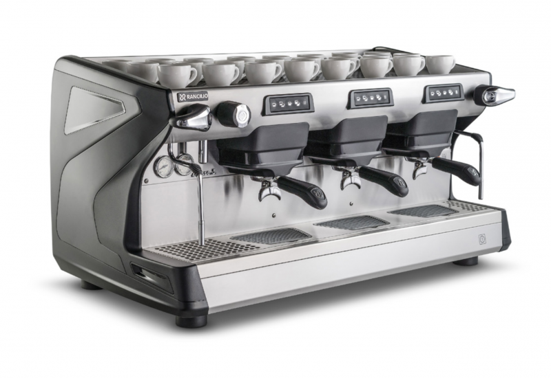 This image is a front-side view of the Rancilio Classe 5 3 group espresso machine in Anthracite Black, with traditional brew group height and USB volumetric dosing controls.