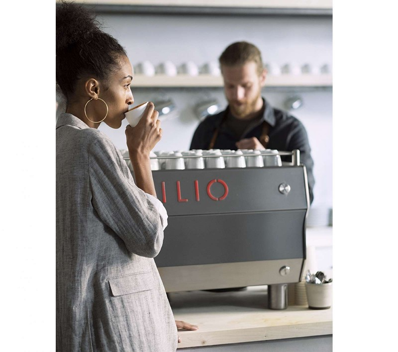 This image is a front-side view of the Rancilio Specialty RS1 espresso machine showcase picture with barista and customer with drink.