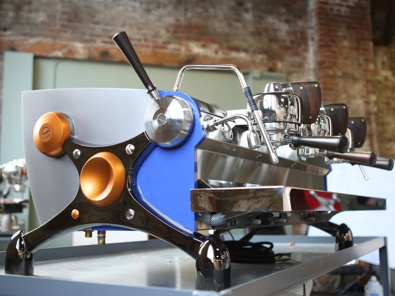 This image is a front-side view of the Slayer Espresso custom machine with custom painted side panels, black nickle plated x-legs, custom painted hubs and accents in Ziricote wood, 3 groups at traditional height with manual dosing controls.