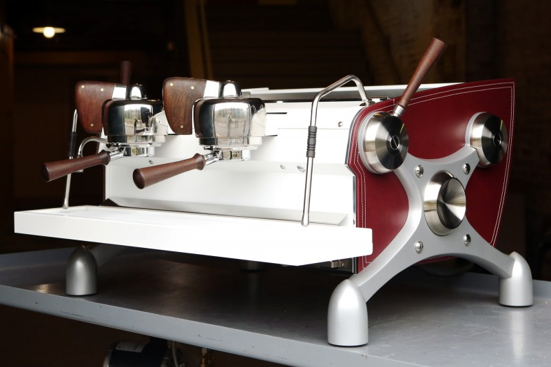 This image is a front-side view of the Slayer Espresso custom machine, leather sides, back/front panel and drip/cup trays powder coated white, x-legs powder coated silver, peruvian walnut wood accents, 2 groups at traditional height, manual dosing.
