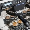 This image is a closeup front view of the Rancilio Classe 7 espresso machine brew groups, with traditional brew group and USB Volumetric Dosing Controls.